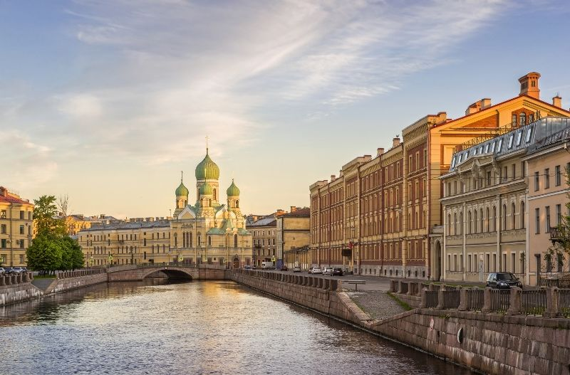 Yellow church with green domes along the river in the morning light city (800x527)